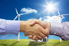 Composite image of hand shake in front of wires. Hand shake in front of wires against house in the middle of a turbine field Royalty Free Stock Image