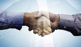 Composite image of hand shake in front of wires. Hand shake in front of wires against low angle view of skyscrapers Royalty Free Stock Image