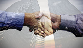 Composite image of hand shake in front of wires. Hand shake in front of wires against low angle view of skyscrapers Stock Photography