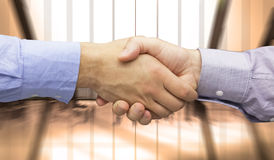 Composite image of hand shake in front of wires. Hand shake in front of wires against room with large window looking on city Stock Photo