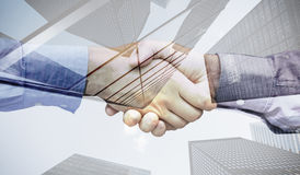Composite image of hand shake in front of wires. Hand shake in front of wires against skyscraper Royalty Free Stock Photography