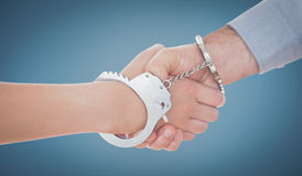 Composite image of handcuffed business people shaking hands Stock Photo