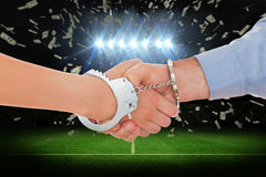 Composite image of handcuffed business people shaking hands Royalty Free Stock Images