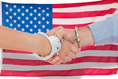 Composite image of handcuffed business people shaking hands Stock Images