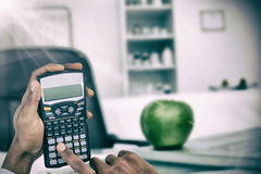 Composite image of hands of businessman using calculator Royalty Free Stock Images