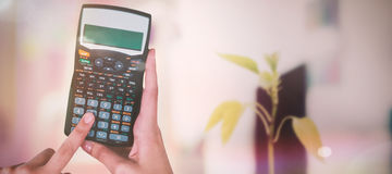 Composite image of hands of businesswoman using calculator Royalty Free Stock Photos