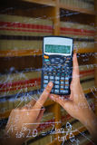 Composite image of hands of businesswoman using calculator Stock Images