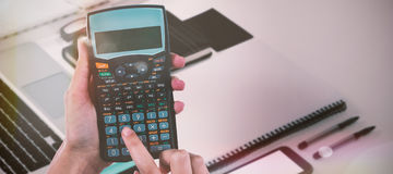 Composite image of hands of businesswoman using calculator Stock Photo