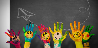 Composite image of hands with colourful smiley faces Royalty Free Stock Image