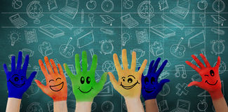 Composite image of hands with colourful smiley faces Royalty Free Stock Images