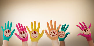 Composite image of hands with colourful smiley faces Stock Photo