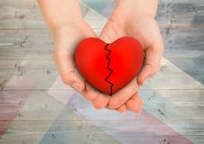 Composite image of hands holding broken heart against wood background Royalty Free Stock Image
