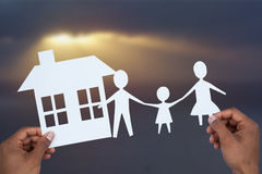 Composite image of hands holding a family with her house in paper Stock Images