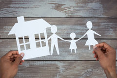 Composite image of hands holding a family with her house in paper Royalty Free Stock Images