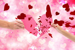 Composite image of hands holding two halves of broken heart Stock Photo