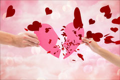 Composite image of hands holding two halves of broken heart Stock Images