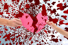 Composite image of hands holding two halves of broken heart Stock Photography