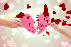 Composite image of hands holding two halves of broken heart Stock Image