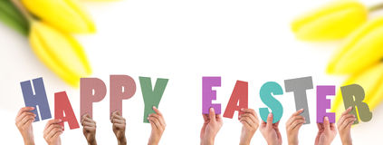 A Composite image of hands holding up happy easter stock images