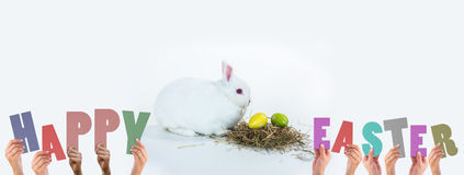 A Composite image of hands holding up happy easter Stock Photos