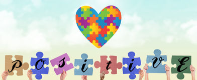 Composite image of hands holding up positive jigsaw pieces. Hands holding up positive jigsaw pieces against blue sky Stock Image