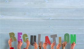A Composite image of hands holding up regulation Royalty Free Stock Image