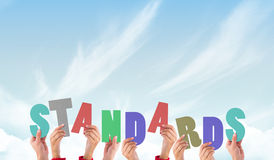 A Composite image of hands holding up standards stock photo