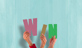 A Composite image of hands holding up win Stock Image