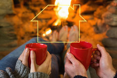 Composite image of hands with red coffee cups in front of lit fireplace. Hands with red coffee cups in front of lit fireplace against house outline Royalty Free Stock Photos