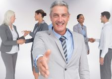 Composite image of Handshake in front of business people with white background Stock Photo