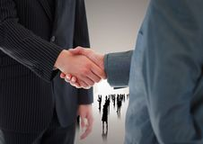 Composite image of Handshake in front of silhouette business people. Digital composite of Handshake in front of silhouette business people Royalty Free Stock Photo