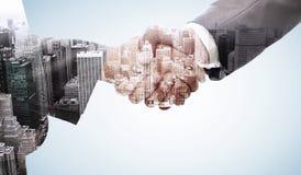Composite image of handshake between two business people Stock Photos