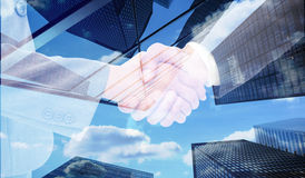 Composite image of handshake between two business people Stock Photos