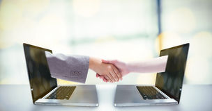 Composite image of handshake between two women Royalty Free Stock Photo