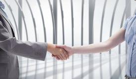 Composite image of handshake between two women Royalty Free Stock Image