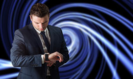 Composite image of handsome businessman checking the time Royalty Free Stock Photos