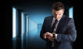 Composite image of handsome businessman checking the time Royalty Free Stock Photo