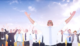 Composite image of handsome businessman cheering with arms up. Handsome businessman cheering with arms up against beautiful orange and blue sky Stock Photography