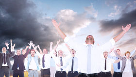 Composite image of handsome businessman cheering with arms up. Handsome businessman cheering with arms up against blue and orange sky with clouds Royalty Free Stock Photo