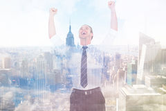 Composite image of handsome businessman cheering with arms up. Handsome businessman cheering with arms up against city skyline Stock Image