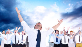 Composite image of handsome businessman cheering with arms up. Handsome businessman cheering with arms up against cloudy sky Stock Photography