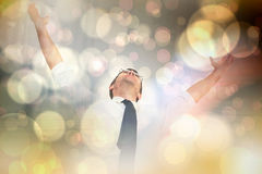 Composite image of handsome businessman cheering with arms up. Handsome businessman cheering with arms up against light glowing dots design pattern Royalty Free Stock Photos