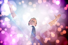 Composite image of handsome businessman cheering with arms up. Handsome businessman cheering with arms up against light glowing dots on purple Stock Photography