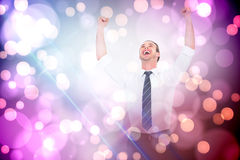 Composite image of handsome businessman cheering with arms up. Handsome businessman cheering with arms up against light glowing dots on purple Stock Image