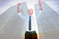 Composite image of handsome businessman cheering with arms up. Handsome businessman cheering with arms up against low angle view of skyscrapers Stock Photography