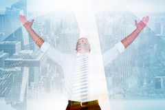 Composite image of handsome businessman cheering with arms up. Handsome businessman cheering with arms up against low angle view of skyscrapers Stock Photo