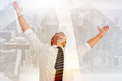 Composite image of handsome businessman cheering with arms up. Handsome businessman cheering with arms up against low angle view of skyscrapers Royalty Free Stock Image