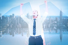 Composite image of handsome businessman cheering with arms up. Handsome businessman cheering with arms up against mirror image of city skyline Royalty Free Stock Images