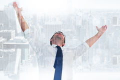 Composite image of handsome businessman cheering with arms up. Handsome businessman cheering with arms up against room with large window looking on city Royalty Free Stock Photo