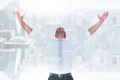 Composite image of handsome businessman cheering with arms up. Handsome businessman cheering with arms up against room with large window looking on city Royalty Free Stock Image